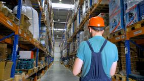 A back view on a warehouse employee walking an aisle at a storage. 4K. stock video footage