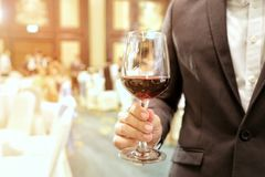 Close of of business man wearing suit holding a glass of wine in the company party with ray yellow light in the background. Royalty Free Stock Photography