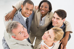 Close business team embracing in a circle smiling up at camera Stock Photography