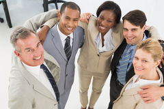 Close business team embracing and smiling up at camera Royalty Free Stock Photo
