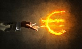Concept of money making with euro currency fire symbol on dark background stock photo