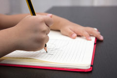 Close of children hands writing on excercise book Royalty Free Stock Photos
