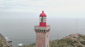 Close clockwise aerial shot of lighthouse on the coast above the ocean with the city in the background in Catalonia stock footage