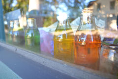 Close on Antique Bottles on Window Sill. Close on colorful antique bottles neatly lined up on a window sill Royalty Free Stock Images