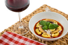 Close of cooked tortelloni in bowl on napkin by wineglass Royalty Free Stock Photo