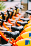 Close Of Cycling Seats In Row Of Colorful Bicycles AVIVA For Rent Stock Images