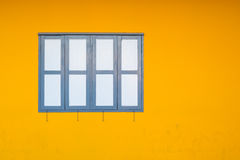 Close Dark Blue Window on Yellow Concrete or Cement Wall Stock Photo