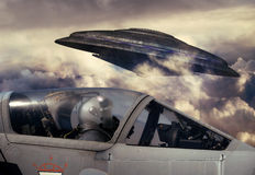 Close encounter. Fighter pilot observing a UFO flying above the clouds Royalty Free Stock Photo