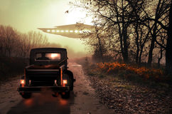 Close encounter on the road. Into the night and the mist, man sat in his car, observing an UFO over the road Stock Images