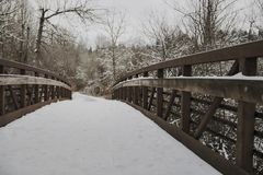 Close, Eye Level Angular View of Snow Covered Wooden Bridge in Wooded Area, Overcast Pale Blue Sky, Daytime stock photography