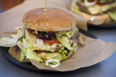Close on fast food unhealthy burger on paper, Stock Image