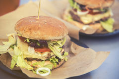 Close on fast food unhealthy burger on paper, vintage effect Stock Photos