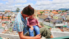 Close Father Little Girl Sit on High House Roof against City stock footage