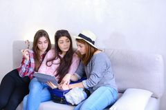 Close female friends use tablet and have fun, sit on couch in ro. Charming three girls friends hold gadget and together choose place to travel, looking at tablet Royalty Free Stock Photography