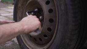Close focus on dirty mechanics hands screwing big wheel bolts while changing flat tire on van stock video