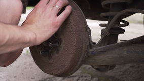 Close focus on dirty mechanics hands screwing big wheel bolts while changing flat tire on van. Hd stock video