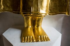 Feet of golden Buddha statue on white stand. Close focus on feet of golden Buddha statue on white stand. Gold foot of Buddha statue. Religion and Travel in Stock Photo