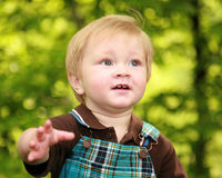 Close focus on a toddler boy's face. Adorable toddler boy looks like he is running and looking up Stock Photos