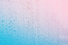Close focus on water drop on colorful glass Stock Photo