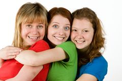 Close friends. Studio portrait of three friendly girls close together in a hug, isolated on a white background Stock Image