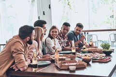 Close friends. Group of young people in casual wear communicating and smiling while having a dinner party royalty free stock photography