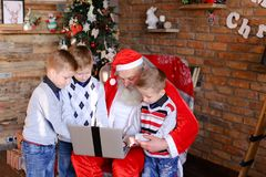 Close Friends Of Children With Santa Claus Use Laptop In Christ Royalty Free Stock Images