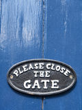 Close the gate sign. Please close the gate sign on blue painted door Royalty Free Stock Images