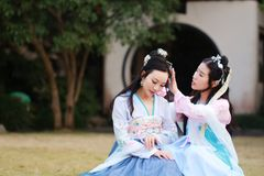 Close girlfriends bestie in Chinese traditional ancient costume. Close girlfriends bestie in Chinese traditional hanfu dress in a garden, ancient chinese hanfu Royalty Free Stock Photography