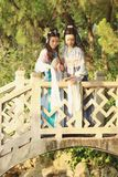 Close girlfriends bestie in Chinese traditional ancient costume play in a garden Royalty Free Stock Images