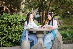 Close girlfriends bestie in Chinese traditional ancient costume play in a garden Stock Photos