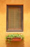 Close glass window on orange wall. Close glass window with wooden frame on orange wall Royalty Free Stock Photos