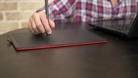 Close. Hand of a teenager boy in a plaid shirt using a stylus. works on a graphic tablet stock video