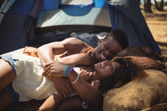 Close of happy couple lying on field against tent Stock Photos