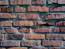 A close-up shot of a rough brick masonry wall lined with red clumsy brick for creativity, textures and background. Royalty Free Stock Photo