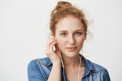 Close-ip portrait of kind gorgeous young redhead girl with blue eyes, wearing earphones while listening music or talking. With friend on phone, smiling and Stock Images