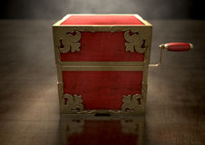 Close Jack-In-The-Box Antique. An ornate antique closed jack-in-the-box mad of red wood and gold trimmings on a dark studio background under a spotlight Stock Images