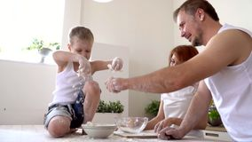 The close-knit family cooks together in the kitchen.. On this video you can see as the family cooks dough. The big family makes a dinner in kitchen. All family stock footage