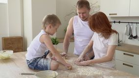 The close-knit family cooks together in the kitchen. On this video you can see as the young family cooks dough for pastries in kitchen. The close-knit family stock video footage