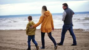 Close-knit family with two children having a walk on the coast. Slow motion steadicam shot of four family members walking at the beach. Parents, little daughter stock footage