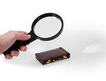 Close look at business. Magnifying glass used to get a closer view on things, burgandy leather Briefcase used to carry items to the office Stock Image