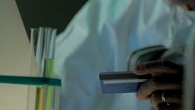 Close look of elderly scientist with laptop and credit or debit card. Shot can be used to demonstrate online shopping of stock footage