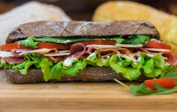 Delicious Homemade Sandwich with ham, peperoni, fresh tomatoes, lettuce and olives. Close look of fresh Homemade sandwich with peperoni, lettuce, tomatoes and royalty free stock photography