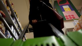 Low angle shot woman in fur coat pulls trolley in store. Close low angle shot woman in fur coat with cross body bag pulls green plastic trolley past shelves in stock video