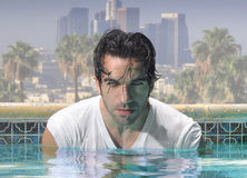 Close man in pool. Close-up portrait of a handsome man in glamorous swimming pool with city background stock photo