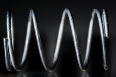 Close metal spring. On a gray and black background Royalty Free Stock Images