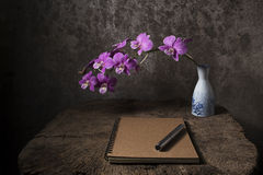 Close note book and purple orchid in  vase on an old wooden tabl Royalty Free Stock Images