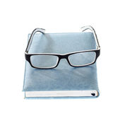 Close notebook and glasses isolated on white. Close blue notebook and glasses isolated on white Stock Photography