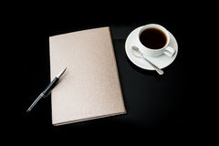 Close notebook, pen and cup of coffee Stock Photography