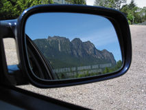 Close Objects. A mountain looms in a car's side mirror reflection. The warning message reads: Objects in mirror are closer than they apear Stock Image