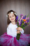 Close ortrait of a little sweet smiling girl holding bouquet of Royalty Free Stock Image